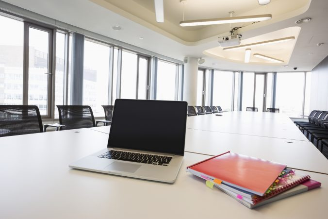 Laptop and files on empty conference table in creative office